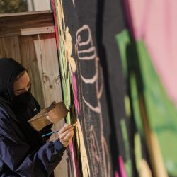 artist concentrates as she paints her mural