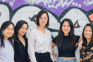Five women pose in front of graffiti wall
