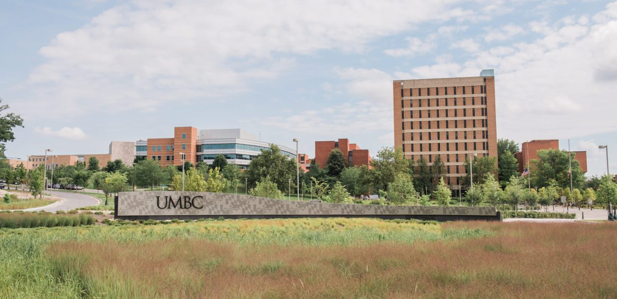 UMBC sign with campus in background