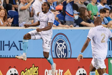 Bell in soccer uniform jumps and pumps arms in victory