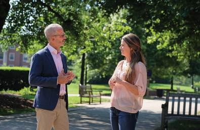 Troy Paino chats with Jennifer Monroe '18 on Campus Walk.