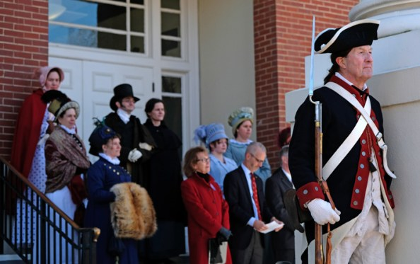 UMW President Troy D. Paino consults the program as he and Fredericksburg Mayor Mary Katherine Greenlaw, in red, prepare to address the crowd before the swearing in. (Photo by Norm Shafer)