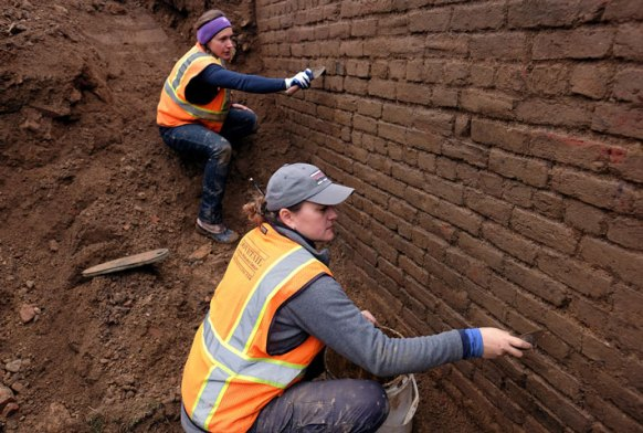 Adriana Lesiuk Moss '11 and Kerri Barile '94 clean a wall from the Ferneyhough Ice House at the site of a park on the Rappahannock River. Built in 1832, Ferneyhough was Fredericksburg's first formally established commercial ice house and was used into the early 20th century.