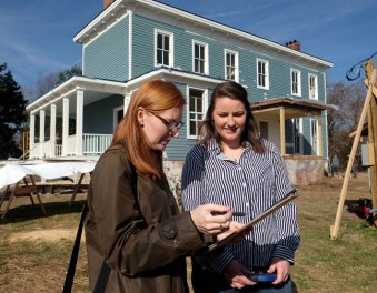 Dovetail's Katherine Watts, left, and Maddie Kelly '19 consult outside historic Sligo in Fredericksburg in March. Dovetail is helping its owners get the home on the National Register of Historic Places.