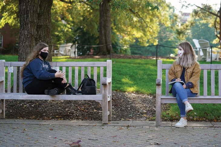 One student per bench? No problem. Students Kira Frazee (left) and Allison Bliss practiced socially distanced bench-sitting one day last fall. [Suzanne Carr Rossi '00]