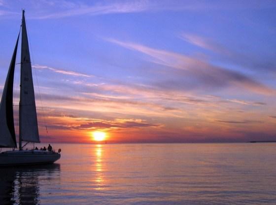 La foto mostra una barca a vela e, sullo sfondo, un tramonto