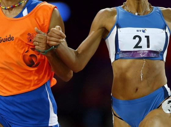 L'immagine mostra un'atleta paralimpica e la sua guida