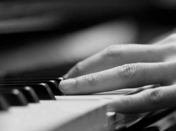 La foto mostra un pianoforte e delle dita che lo suonano