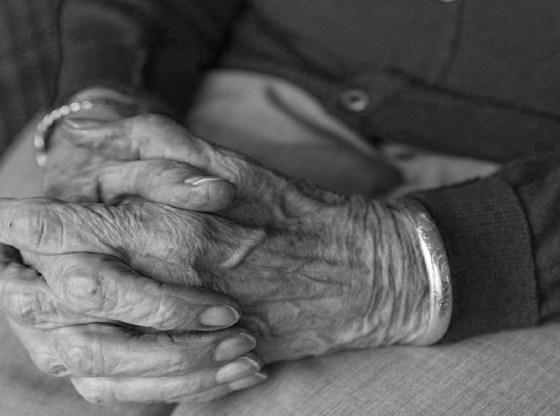 La foto mostra le mani giunte di una persona anziana