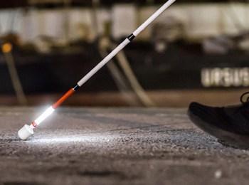 La foto mostra un non vedente che cammina con l'ausilio di un bastone luminoso