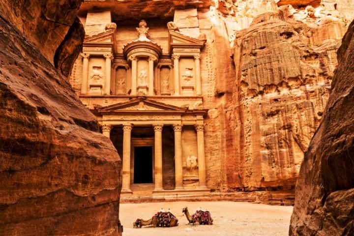 Due cammelli riposano di fronte all'Al-Khazneh, uno degli edifici scolpiti nella roccia di Petra in Giordania