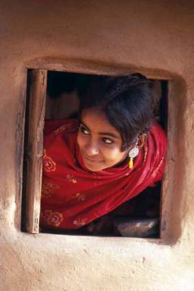 Hindusi to ludzie życzliwi i otwarci wobec przybyszów, jak ta piękna dziewczyna wyglądająca ciekawie z okna wiejskiego domu.