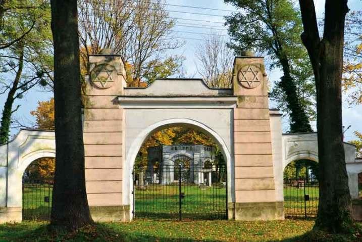 """Brama """"nowego"""" cmentarza żydowskiego, w głębi ściana frontowa domu przedpogrzebowego."""