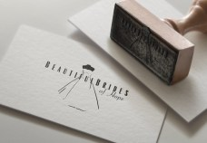Closeup of rubber stamp of Beautiful Brides of Hope bridal couture logo. The symbol is set within and amongst type, showcasing the elegant, finessed bridal illustration and type that together create an integrated singular brand expression.
