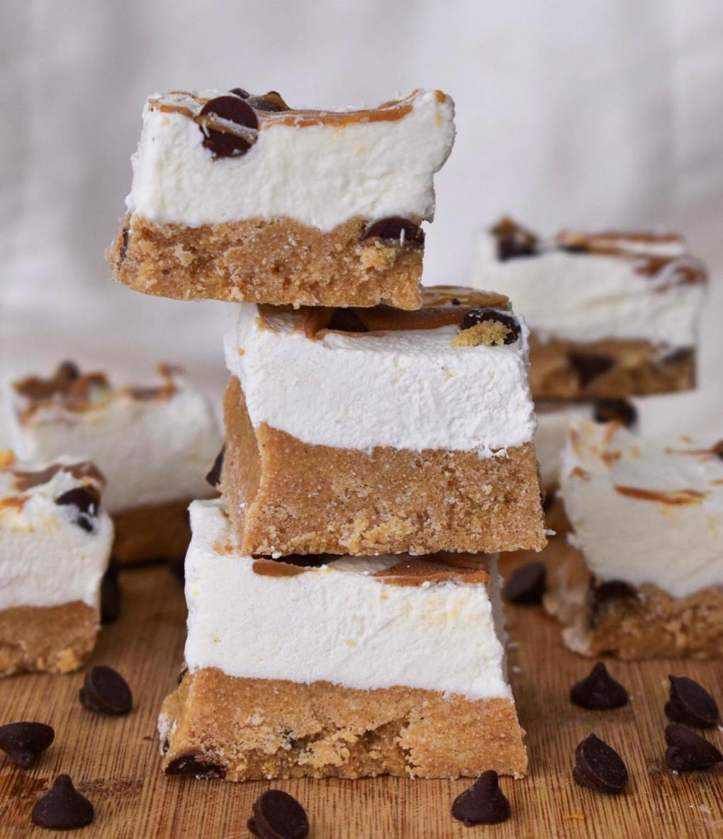 three vegan cheesecake bars stacked on eachother with a cookie dough base. Chocolate chips and more cheesecake bars are shown in the background.
