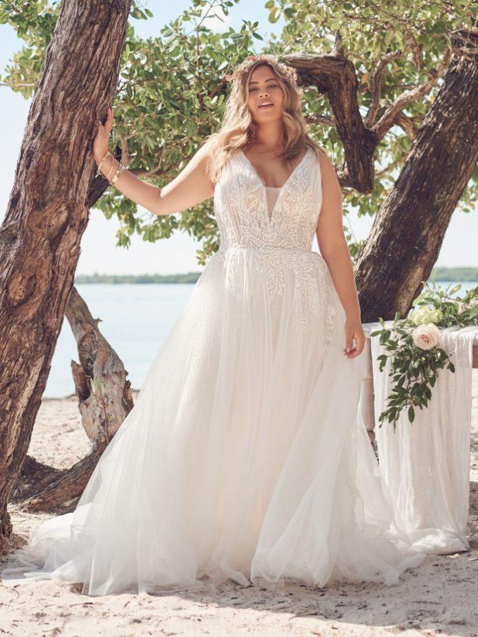 Bride wears an affordable plus-size A-line wedding dress named Jenessa by Rebecca Ingram