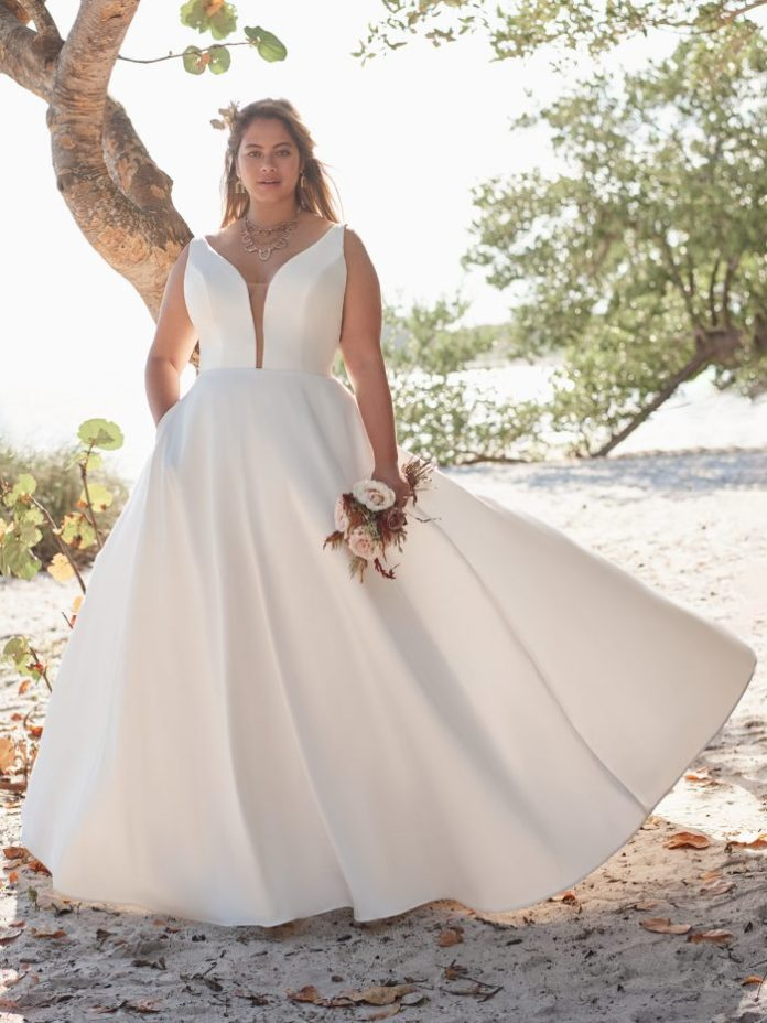 Bride wears a large satin ball gown wedding dress named Pearl by Rebecca Ingram