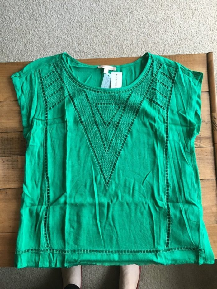 Green blouse with laser cut perforations in the front
