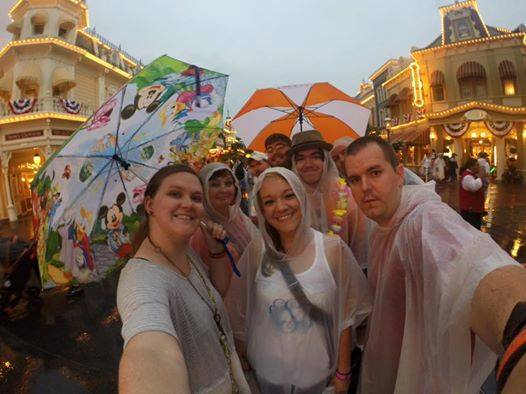 A family holds umbrellas and poses on Main Street, USA