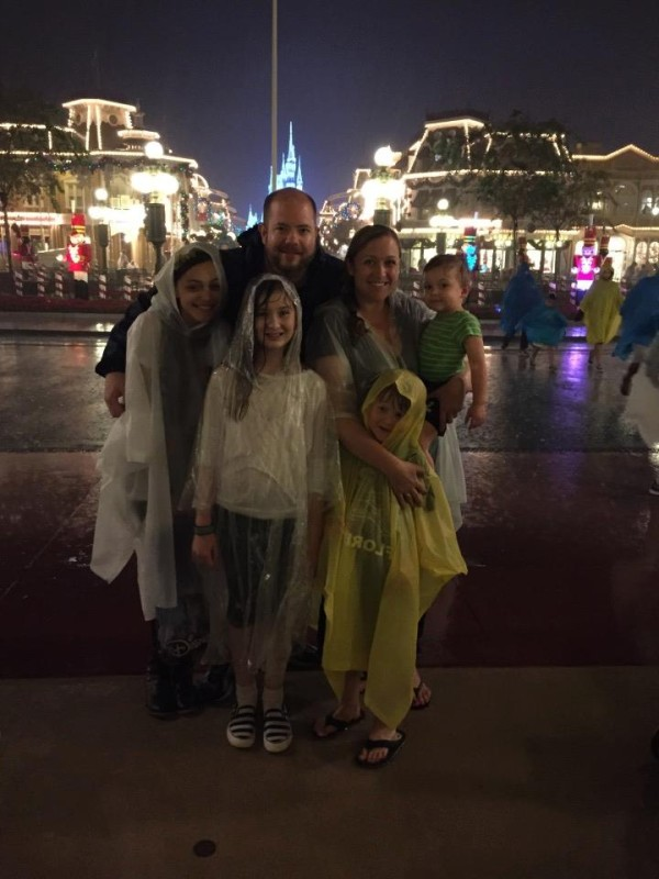 Family stands in the rain at Magic Kingdom