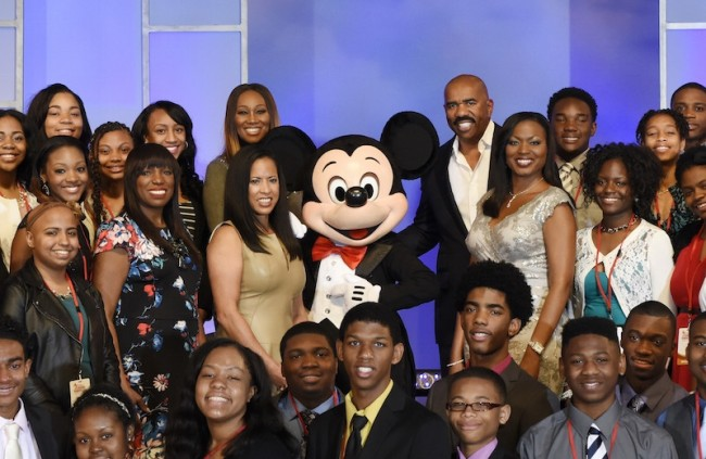Disney Dreamers join singer Yolanda Adams (back row left of center), entertainer Steve Harvey (back row right of center), Mikki Taylor, editor-at-large for Essence Magazine (second to the left of Mickey Mouse), Michelle Ebanks, president of Essence Communications, Inc. (left of Mickey Mouse), Mickey Mouse, and Tracey D. Powell, executive champion of Disney Dreamers Academy (to the right of Mickey Mouse), March 8, 2015 to celebrate the commencement of Disney Dreamers Academy with Steve Harvey and Essence Magazine at Walt Disney World Resort. (Todd Anderson, Photographer)