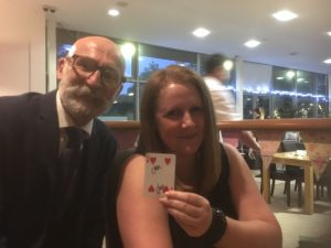 Woman holding a signed laying card accompanied by magician
