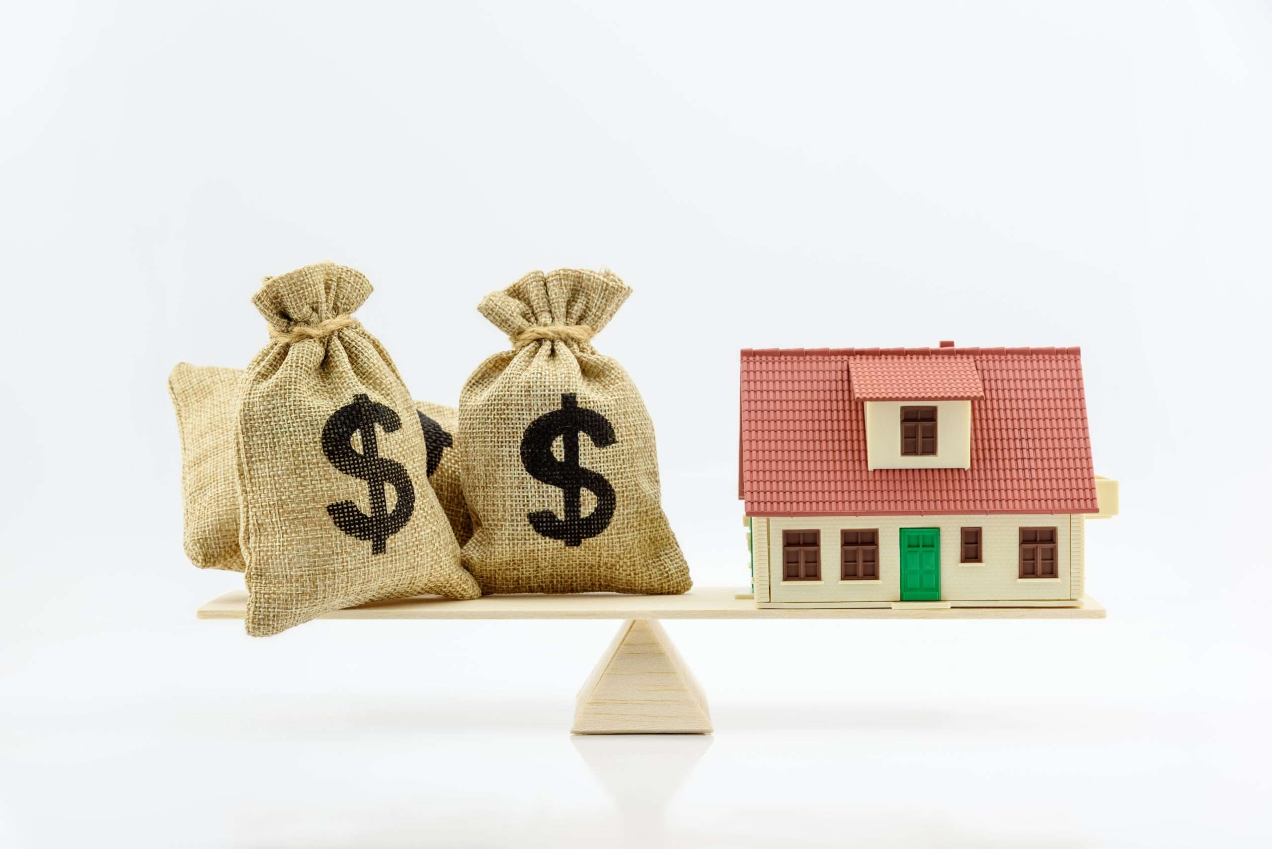 three bags of money balanced against a house