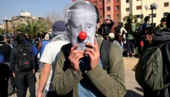 Joven con máscara de anciano en manifestación contra la política tradicional
