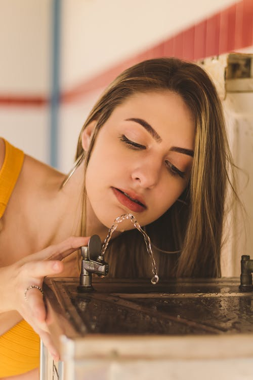 Beautiful women Drinking Water from a water Fountain