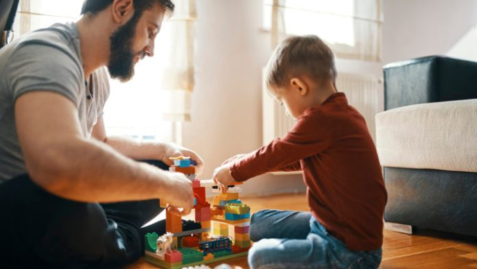 Father And Son Sitting On The Floor Playing Together With Building Bricks