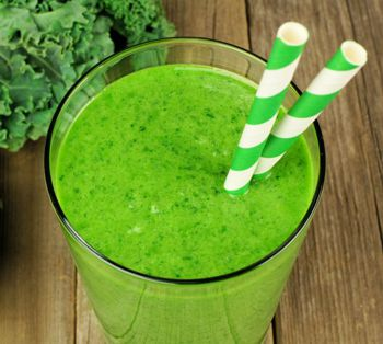 Healthy green kale smoothie in a glass with straws on wood background
