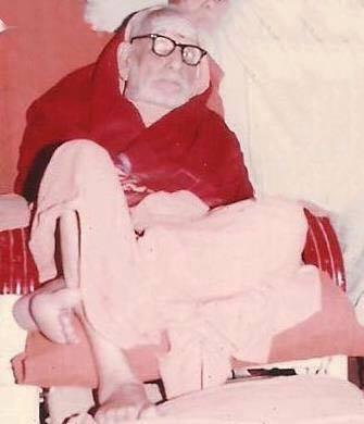 Periyava_sitting_on_cane_chair_with_one_leg_on_stool