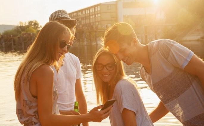 Group Of Cheerful Friends Having Fun Near Lake Using Smart Phone