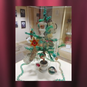 This late 19th century German feather tree is filled with Victorian-era ornaments. There are embossed cardboard Dresdens, scrap ornaments trimmed with tinsel and spun glass, glass balls, and tin-lead alloy reflector candle-holders.  <br><br>Gift of Alice Resch Powers, 78.71, 87.12; Edith Wilms, 82.69; Maureen Creager, 85.11