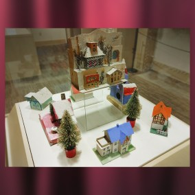 "Cardboard ""Putz"" village with bottlebrush trees. Decorative Christmas villages like this one have roots in 18th Century Moravian culture. These buildings were made in Germany and Japan.  <br><br>Gift of Maureen Creager, 85.11.160"