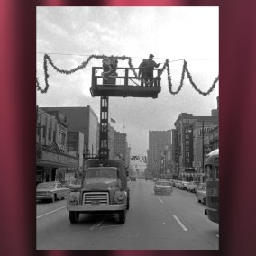 A street crew decorates West Federal Street with a Santa Claus cutout and pine roping in 1964. Original photograph by Paul Schell. <br><br>Gift of Evelyn Schell, 2009.056.01.059.011