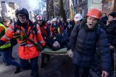 An Interior Ministry member, who was injured during clashes with anti-government protesters, is transported on a stretcher in Kiev