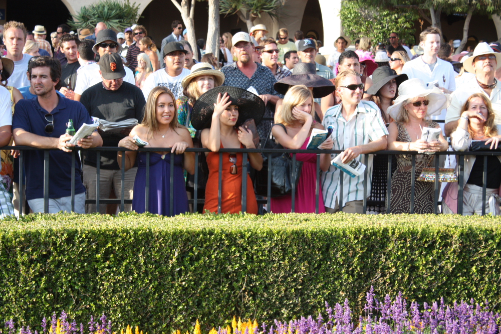 Rail birds crowd the paddock fence to get a look at the horses before the Opening Day nightcap