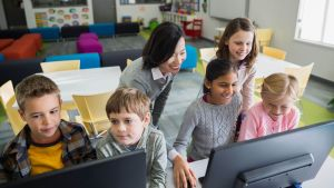 groups of students and teacher in classroom viewing digital content