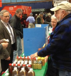 MSBA booth at Maine's 2014 Agricultural Trade Show. Nick Kelley (Western Maine Beekeepers Association) shows  a sampling of Maine honey.