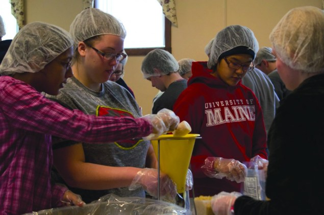 University of Maine students Sierra Crosby, Brigitte Parady, and Aliya Uteuova help pack some of the 20,000 meals to be distributed in the Greater Bangor area for the MLK day of service in Old Town this past weekend.
