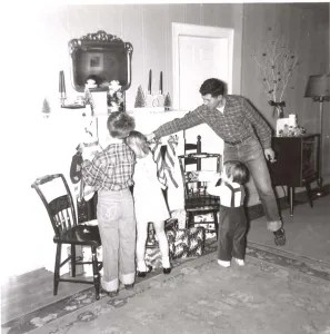 Dad helps John, Kate and Sara hang their stockings.