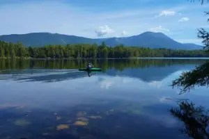 Liz kayaks on Daicey Pond with Katahdin in the background.