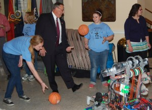 """Governor LePage and Messalonskee High School students play with basketballs ejected by the school's robotics team, """"Infinite Loop,"""" which participated in the FIRST Robotics World Championship in St. Louis in April."""