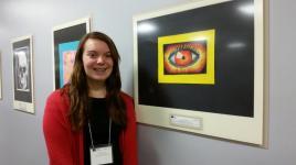 Freshman Molly Wasilewski poses next to her artwork