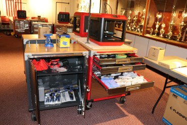 The STEAMRoller Cart includes: Seville Classics UltraHD 2-Door Rolling Cabinet and a 6-drawer Rolling Storage Cabinet, Vise, Portable Vise Table, Power Strips, Cordless Orbital Hand Sander, Corded Orbital Hand Sander, Power Drill, Impact Power Drill, Rotary Dremel Tool, Irwin Clamps, Kobalt 100-Piece Household Tool Set with Hard Case, Hand Tool Bag, Hammer, Locking Pliers, Tape Measure, Speed Square, Spade Bits, Flash Forge 3D Printer, 3D Printer Tool Set, Frog Tape, Duct Tape, Rocketbook, FriXion Pens, iPod Touch & Case, Tripod, Raspberry Pi, Soldering Iron, Scrappy Circuits, Safety Goggles, Disposable Gloves, Breakout of the Box DRAWER, and a Breakout EDU Kit.