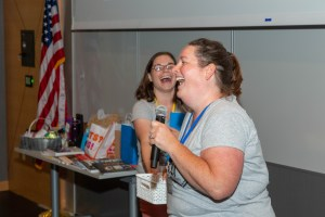 Educator holding microphone laughing