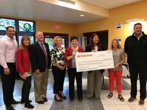 School administrators standing holding a large check from State Farm