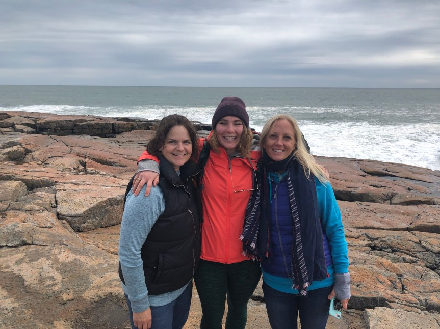 Three people standing together on the rocks with the ocean in the background