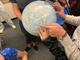 hands pointing on a globe